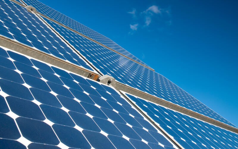 A group of blue solar panels reflect the sun with a blue sky in the background. What is better to connect solar panels in a series or parallel?