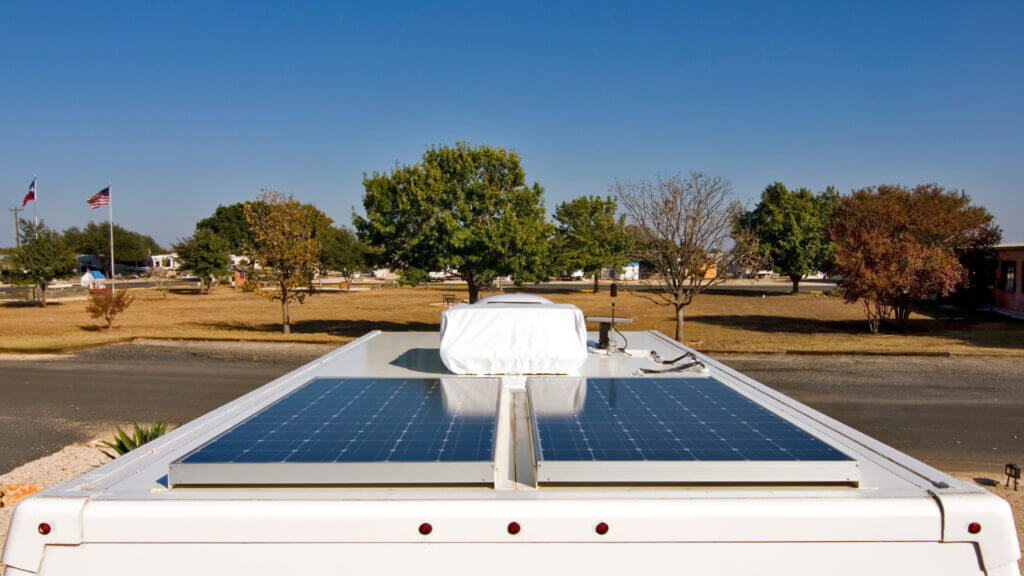 The roof of an RV with two solar panels installed parallel to each other with trees and flags in the background.