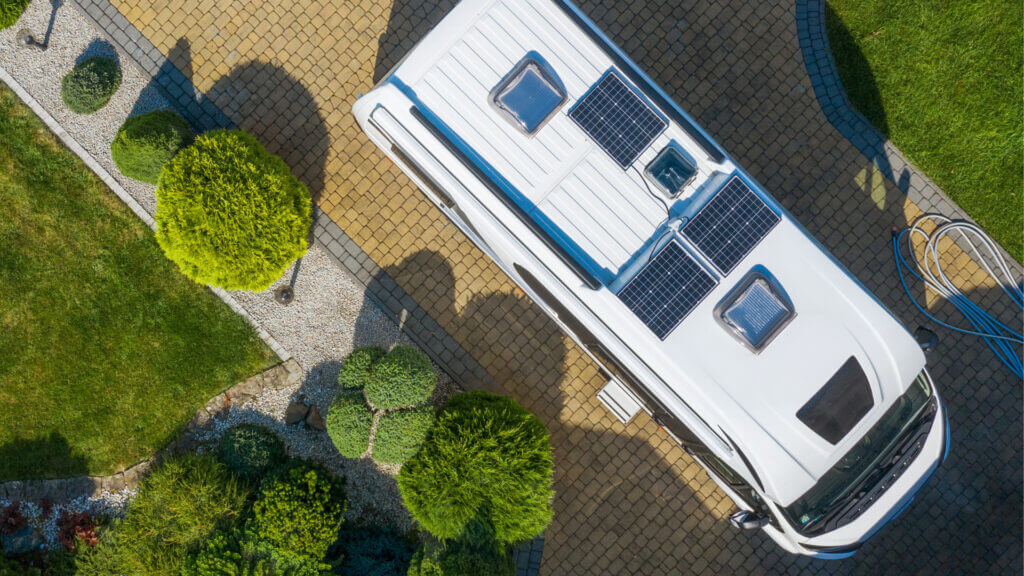 The roof of an RV parked in a brick driveway with solar panels wired via a series.