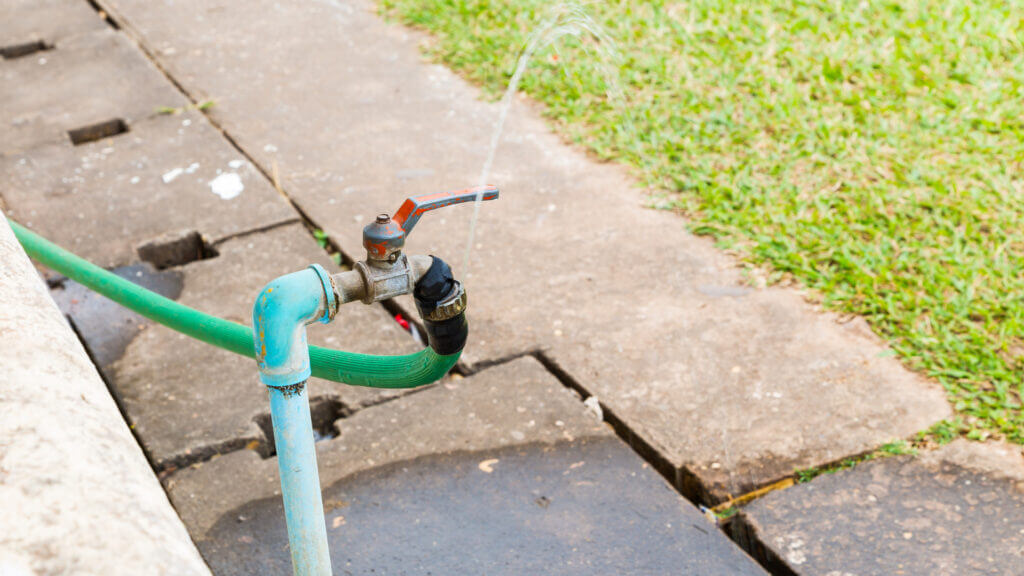 A hose spigot sprays water out and gets the sidewalk everywhere.