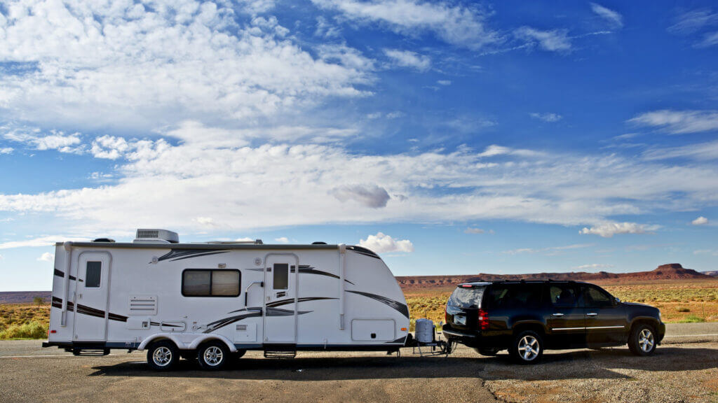 An SUV tows a large travel trailer in the desert. If they want to rent one for a vacation, how much does it cost to rent an RV?