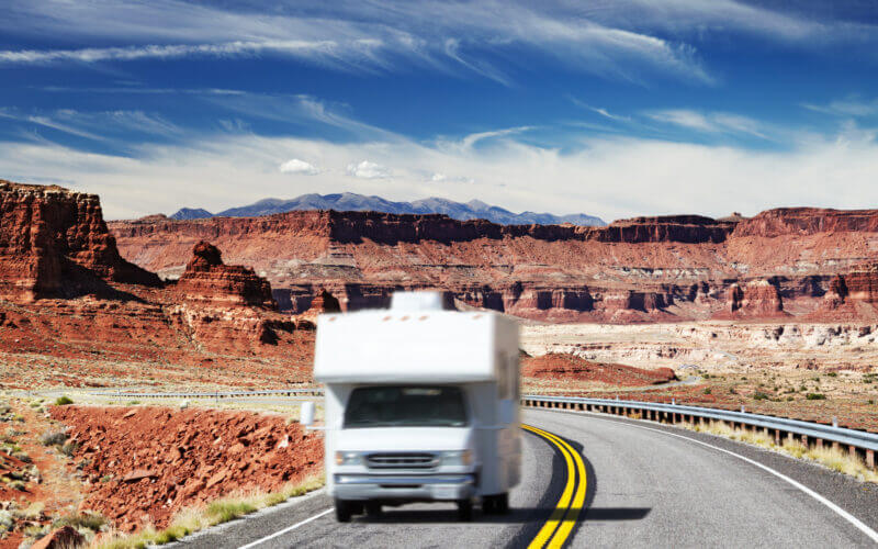 An RV drives down the highway in a blur in the desert (maybe Grand Canyon?). If you wanted to get one for a vacation, how much would it cost to rent an RV?
