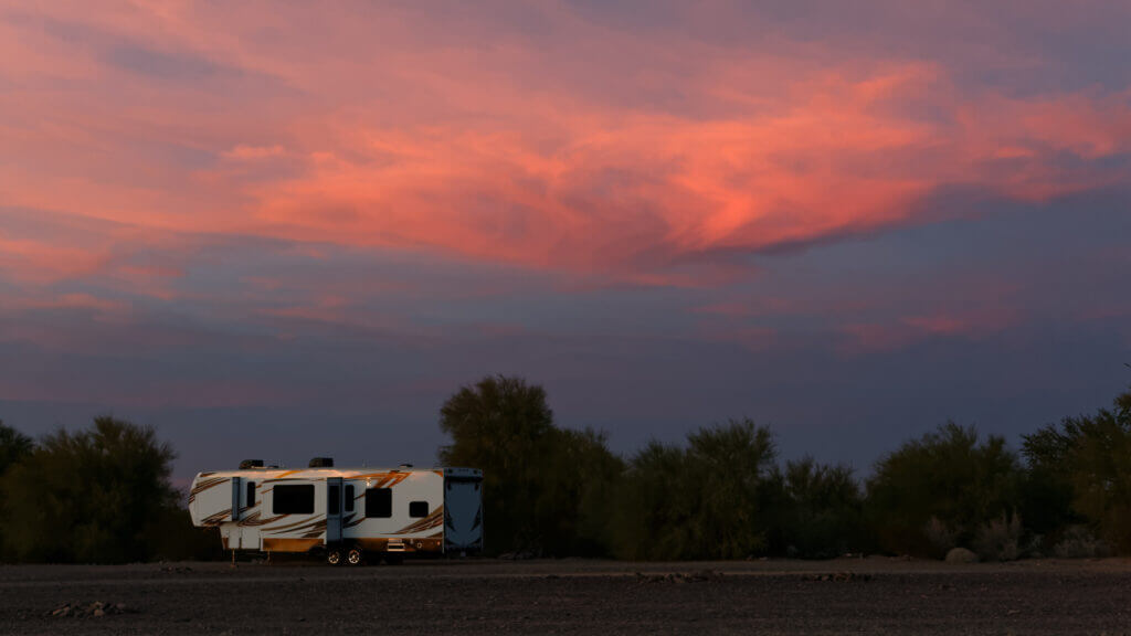 A big RV is boondocking and there is a lovely pink sunset caught in the clouds overhead.