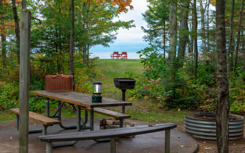 A campsite tucked into the trees looks out onto Lake Michigan with two camping chairs already set out on the shore. These are the 12 best camping spots along Lake Michigan!