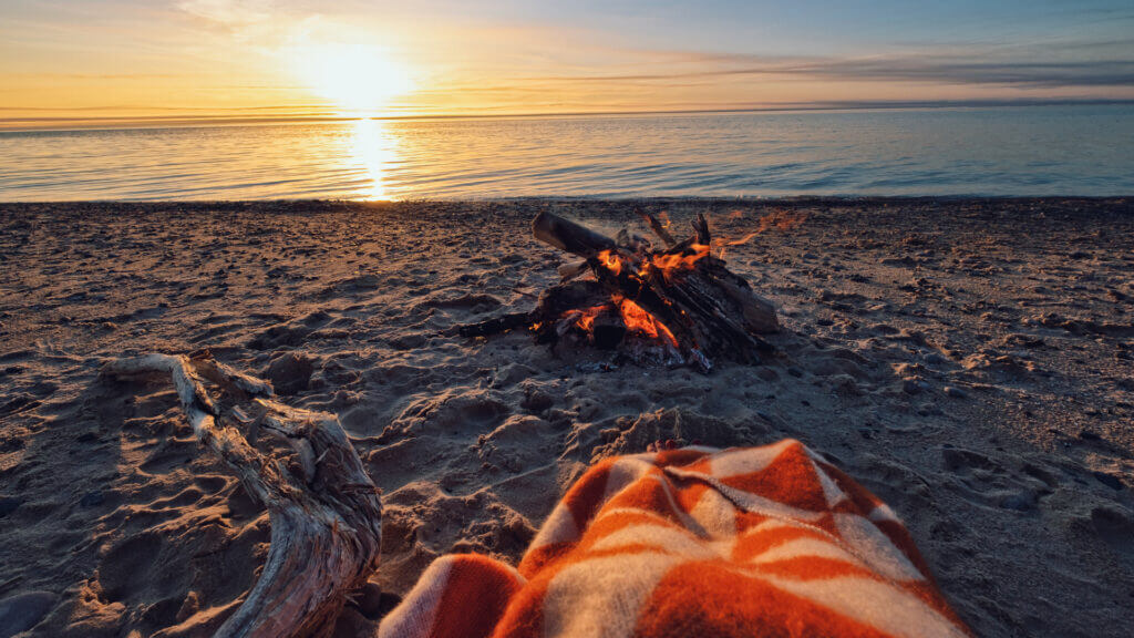 A gorgeous sunset is seen over Lake Michigan while a camper is tucked into an orange and white blanket with a beach bonfire blazing on the shore.