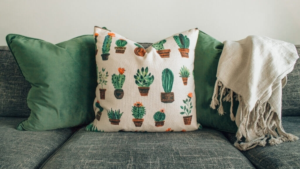 A grey couch has 3 green and cactus throw pillows and a cream throw blanket to make this RV feel more like a house.