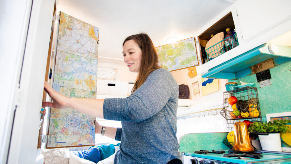 A woman reaches into the cupboard in her RV that has a unique blue backsplash in the kitcken, and customized map wallpaper in the cupboards to make this RV feel more like a house.