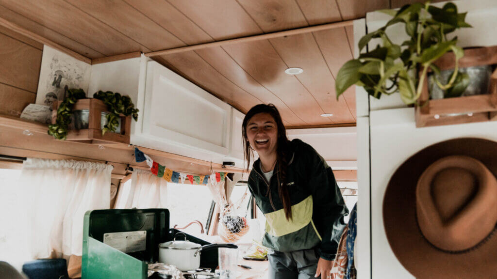 The inside of an RV feels like home with a girl smiling inside, plants and wall art, and customized curtains to replace the factory ones.