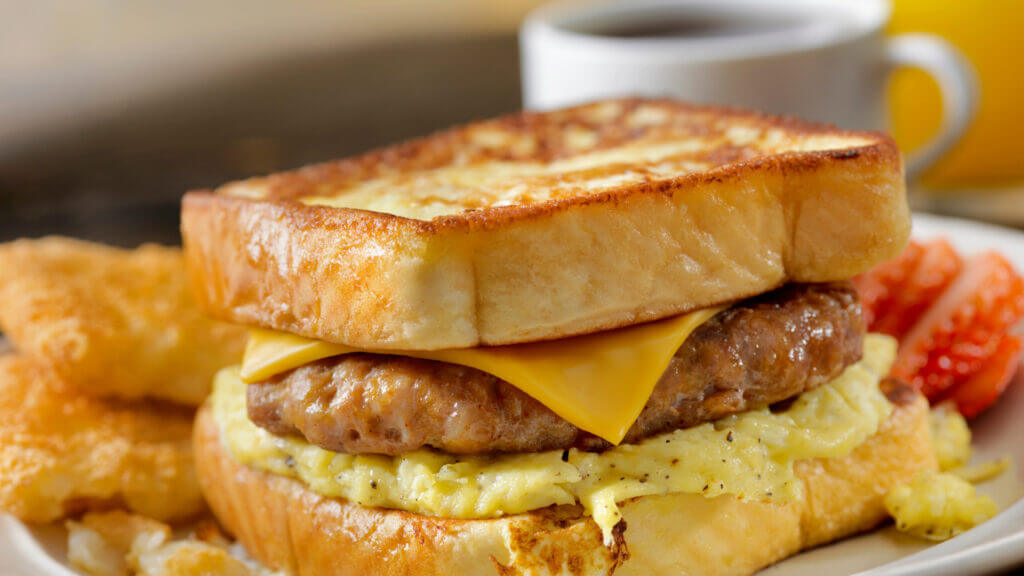 A glossy french toast sandwich that was made on a blacktop griddle is stuffed with sausage, cheese, and scrambled eggs so you get a rich mix of savory and sweet in every bite.