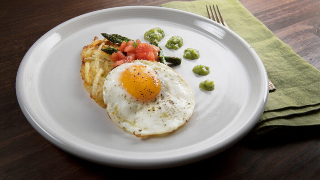 A tex mex haystack is all cooked on the blackstone griddle and is a hash brown base with eggs on top and topped with crumbled bacon, salsa, and a sour cream mix.