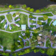 An aerial view of an RV park surrounded b y water and greenery which would be an ideal location to live in your RV full time.