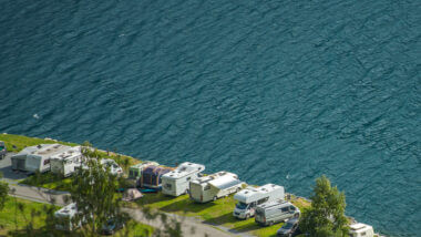 A gorgeous aerial view of an RV park with RVs camped along an oceanside cliff, but what is the average cost of an RV park?