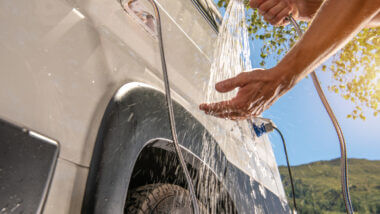 A hand tests the water temperature outside their RV after they finished installing a new tankless water heater into their RV.