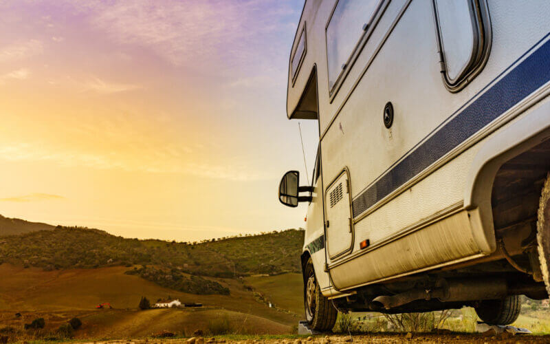 An RV is parked facing a sunset over hills and it is level thanks to RV levelers under the wheels. Did they pick between the camco camper leveler vs andersen?