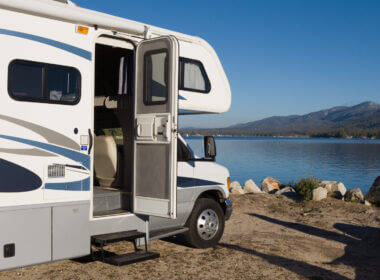 A white rv parked near water has the door open and some steps that can be upgraded to one of these listed best RV steps!