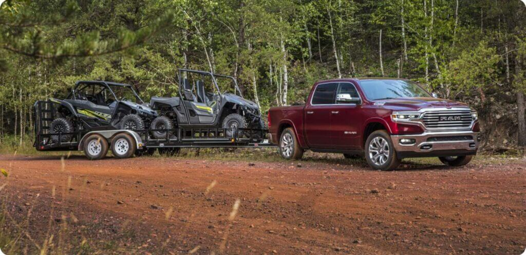 A red Dodge Ram 1500 tows a trailer with two Gators across a red dirt road.
