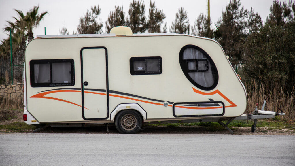 A white travel trailer rental is ready to be hitched up to a car and towed along on an adventure.