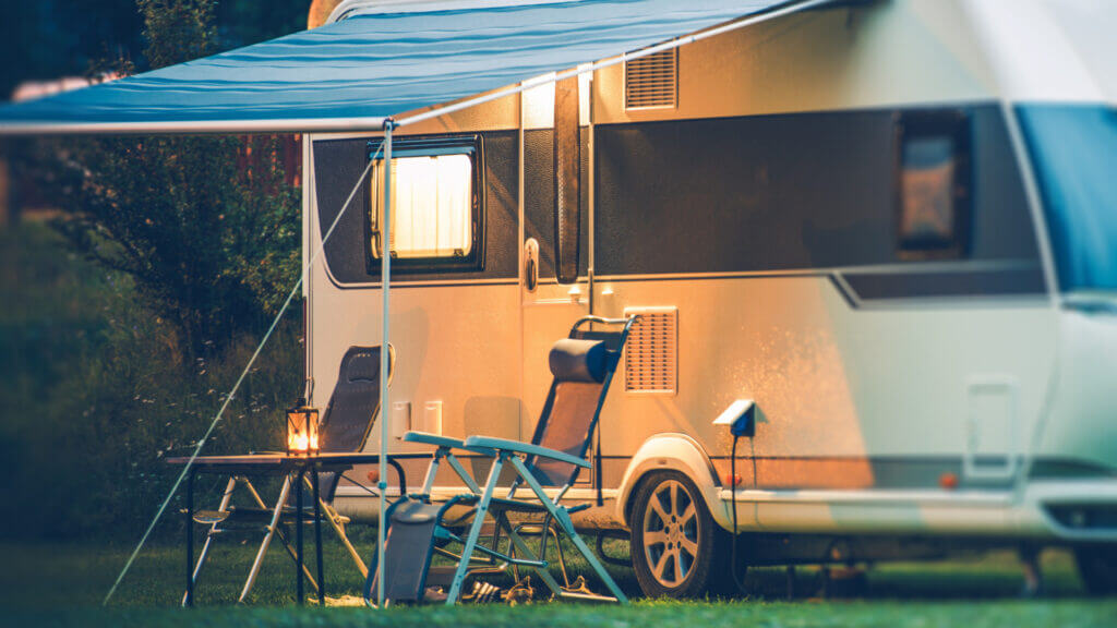 A white travel trailer is set up for camp with chairs outside and an overhang to protect from the sun.