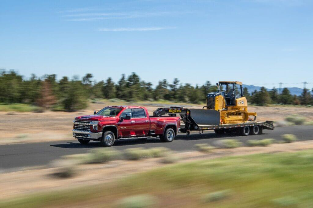 A 2021 Silverado 3500 HD LTZ tows a tractor on a trailer along a highway. It definitely is a great truck option for towing a fifth wheel RV!