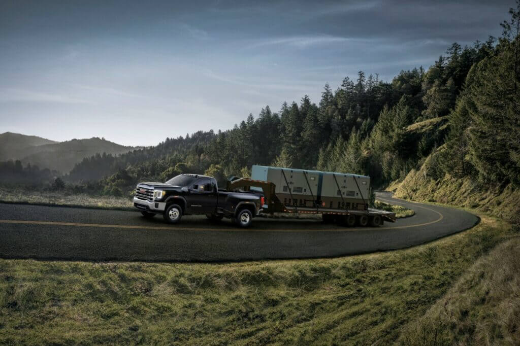 A GMC Sierra 3500HD tows large cargo up a hill easily.