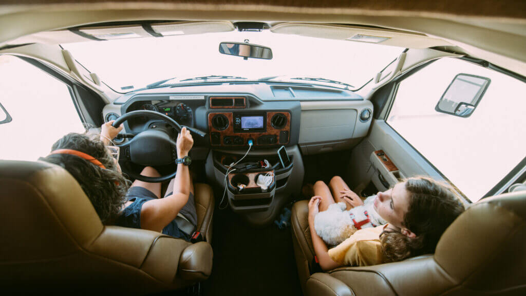 A mom and daughter sit up front in their rented RV while on a road trip.