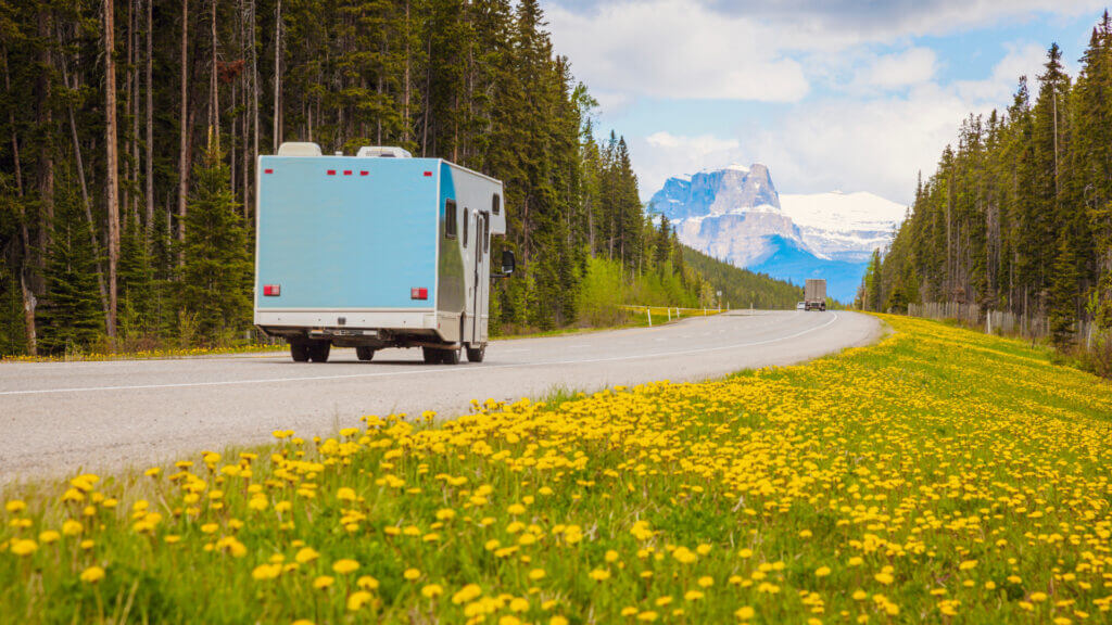 A rented RV is driving down a highway into Glacier National Park, a great road trip destination!