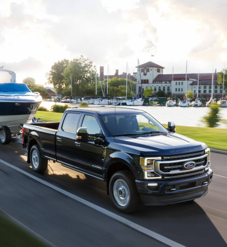A Ford F-350 cruises down a road across from a marina towing a boat for a day of fun.