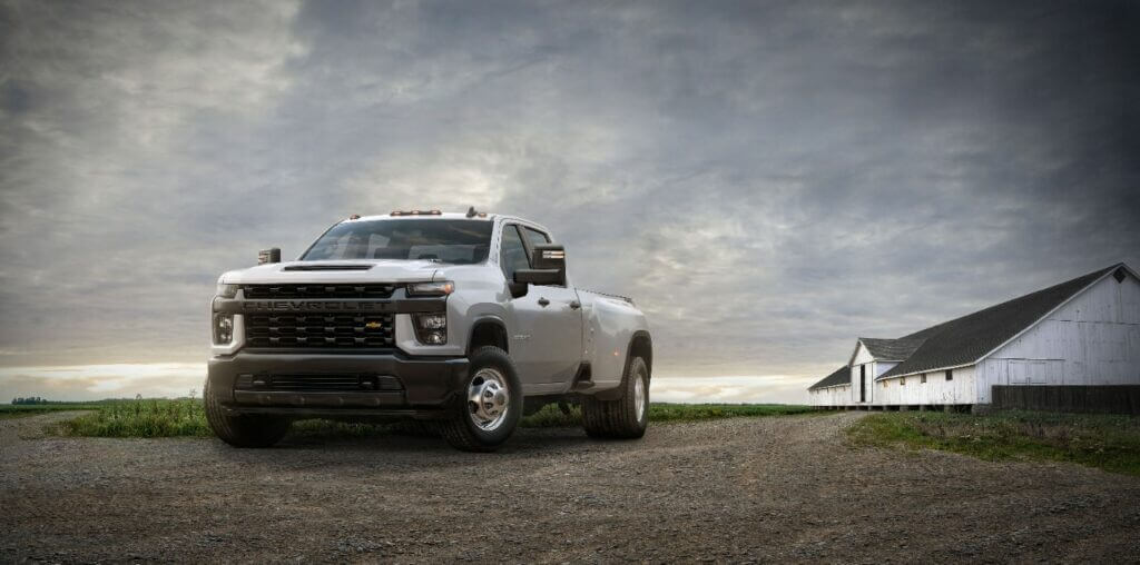 A white 2020 Chevy Silverado 3500 HD dually truck is parked on a farm.
