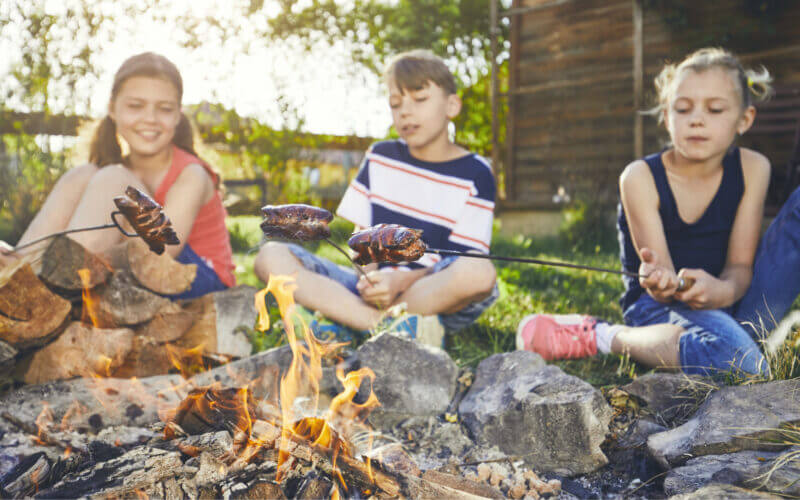 Kids sit in front of a campfire roasting hot dogs but can upgrade their campfire dinners with one of these recipes!