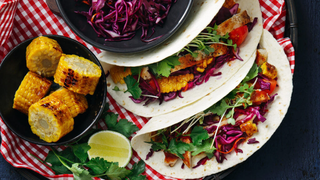A delish lunch idea on your blackstone griddle is chicken cajun tacos with some lime and corn on the side!