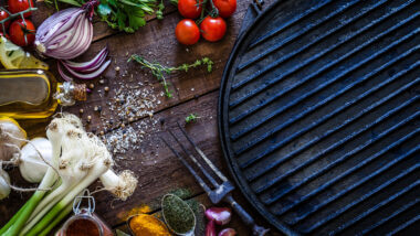 A blackstone griddle is surrounded by spices and veggies and ready to cook some delicious lunch recipes.