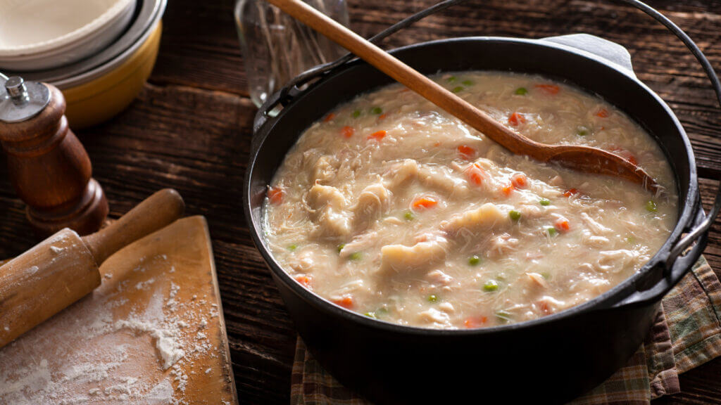 A dutch oven is full of chicken and dumplings on a wooden camping table.