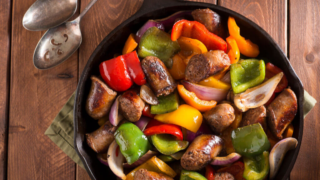 An easy and filling campfire lunch is brats, bell peppers, and onions! You can cook them on a stick or in a cast-iron skillet.