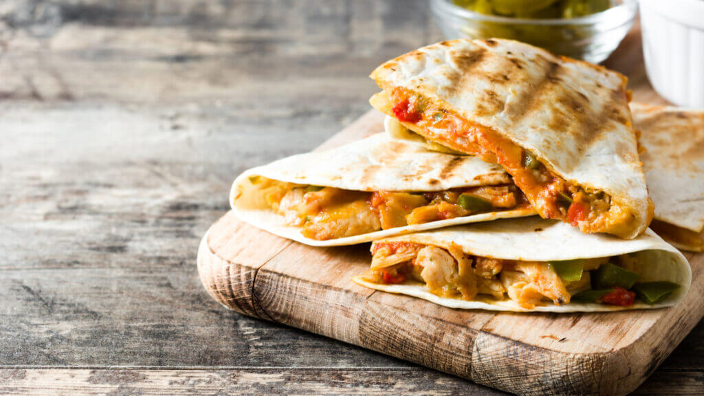 BBQ chicken quesadillas are stacked on top of each other after being cooked over a campfire.