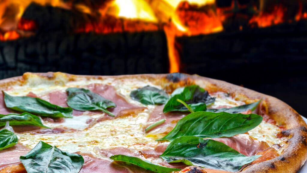 Campfire pizza get's a delicious charred crust and you can customize it to your preference. This pizza has ham and basil and mozzarella on top.