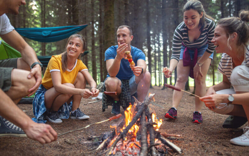 A group of friends cook some delicious lunches over the campfire.