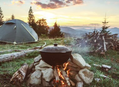 A scenic mountain camping scene with a cast iron pot on top of a fire and the tent among the trees as the sun rise. Try these camping tips and tricks to solve common camping problems!