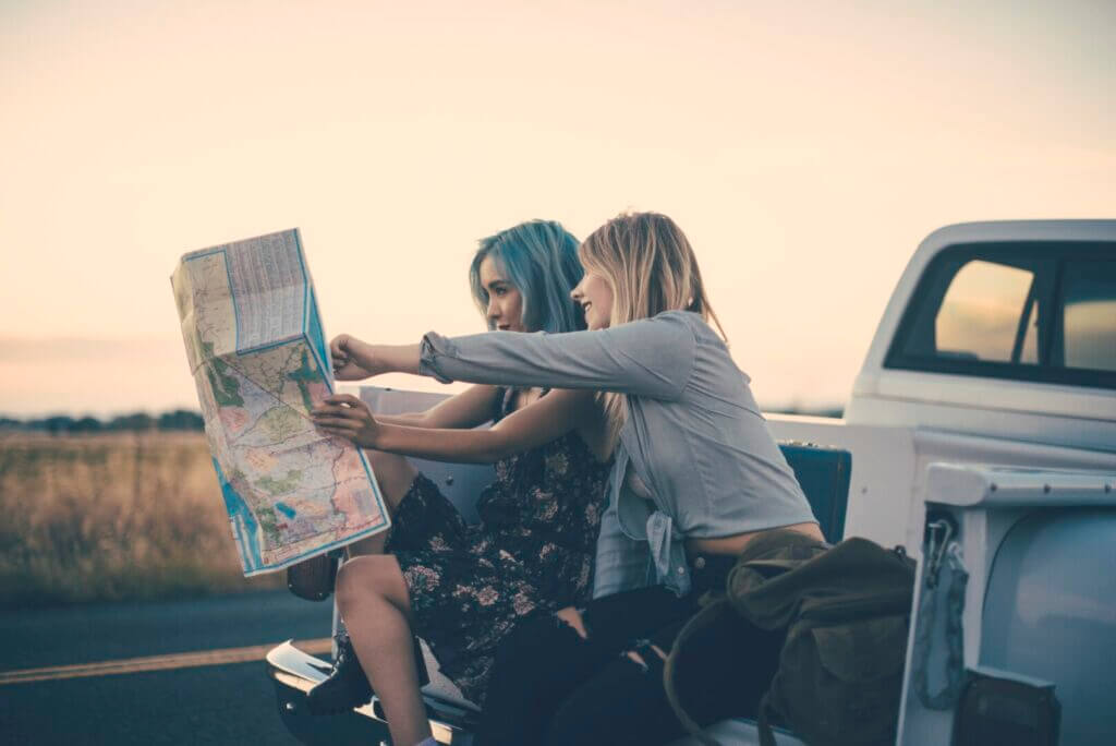 Two girls sitting on the bed of a truck looking at map planning their summer road trip.