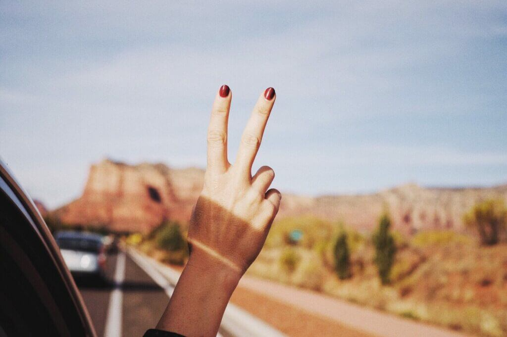 Woman with her hand out the window making the peace sign just starting her summer road trip.