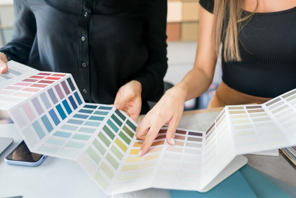 A man and woman looking at different paint color swatches. Painting is a big unique rv decorating idea, as it changes the whole room.