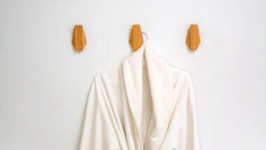 A white robe hangs on the wall thanks to Command Strip products, so you don't have to drill into the walls of your RV to hang things up!