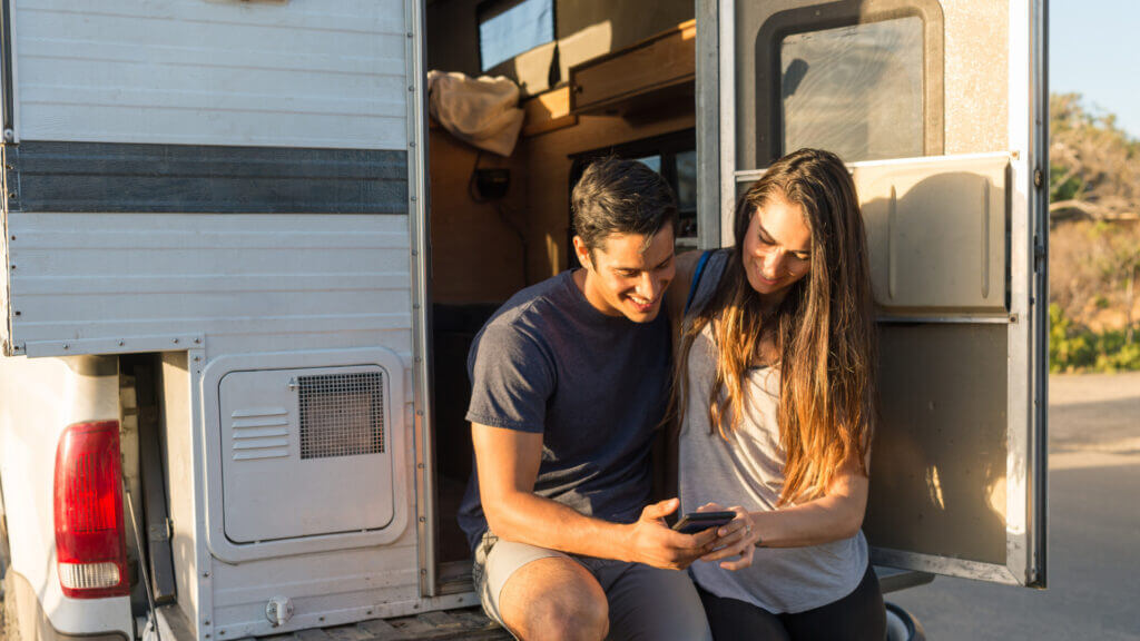 A couple uses RV apps to decide where they are going to camp next in their truck camper.
