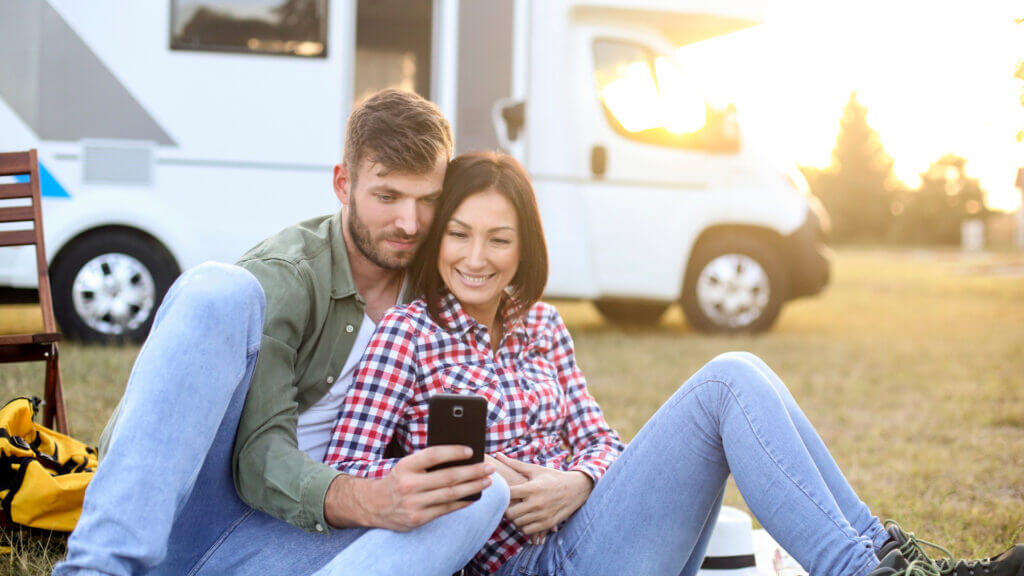 A couple sit in the grass in front of their RV and use RV Apps to plan out the next destination in their trip.
