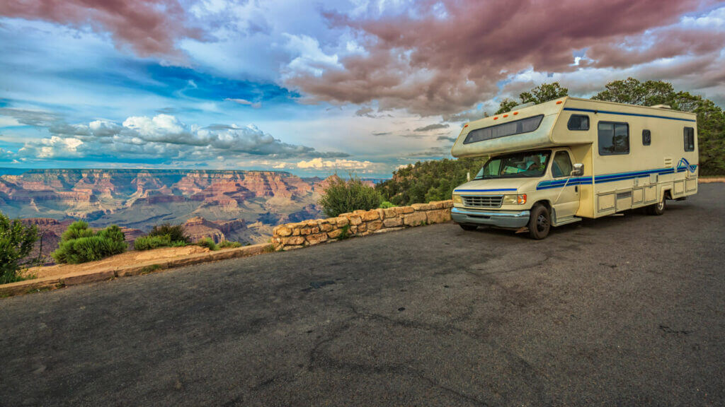 An RV is parked along the rim of the grand canyon while on their trip.