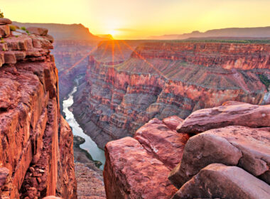 The grand canyon glows red orange with the sun setting on the horizon and the river glows below. A great place to visit in your RV.
