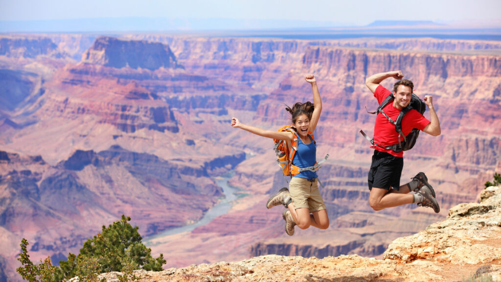 A couple jumps for joy because they are having the best time on their Grand Canyon RV trip.