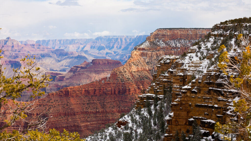 The Grand Canyon is dusted with snow along the rock layers. The best time for your RV trip is september, before its too cold and snowy.