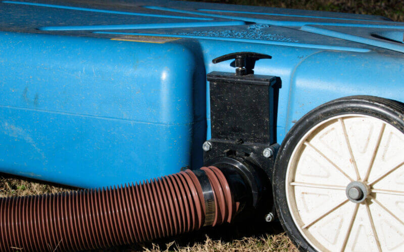 A Barker Portable RV waste tank is connected to the RV and known for it's blue color.