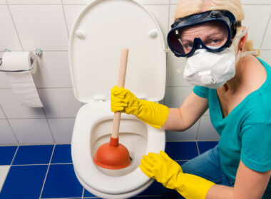 A woman wears a mask, gloves, and goggles to tackle the disgusting but necessary task of unclogging a toilet. How do you unclog an RV toilet?