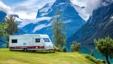 An RV is parked on a grassy hill next to a stunning glacier lake set in the mountains. By using a levelmate pro they can ensure that their RV is level and secure.